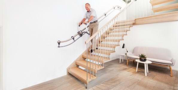 Man walking down a set of stairs using the AssiStep handle and railing